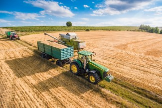 combine-harvester-pouring-grain-into-trailer-towed-by-tractor-picjumbo-com